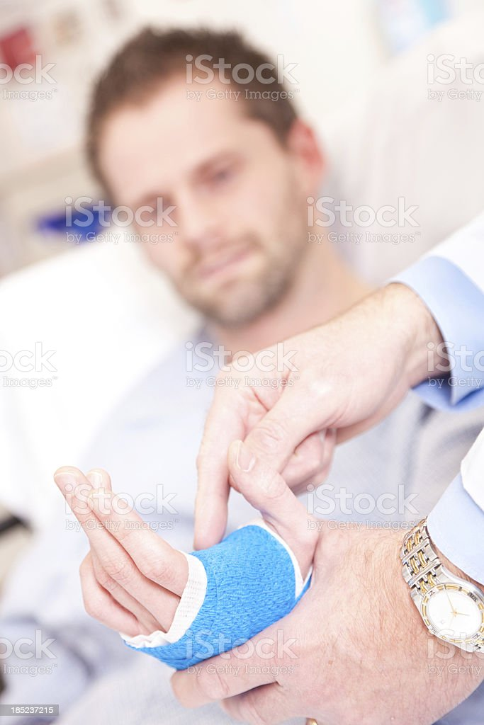 Doctor pointing to injured hand in hospital royalty-free stock photo