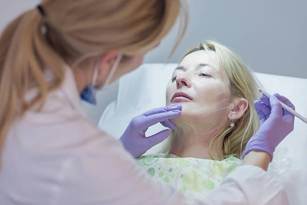 arzt vorbereitung ältere frau mit botox-spritze - nadeldesigns stock-fotos und bilder
