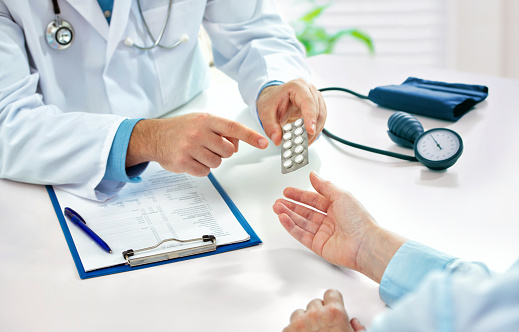 Doctor consulting female patient about pills and dicsussing health treatment sitting in the office at the desk. Medicine and health care concept