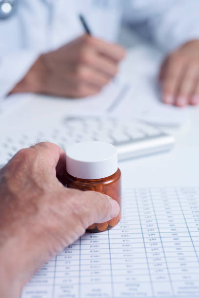 doctor prescribing pills to a senior man closeup of a caucasian doctor man, in a white coat, signing a prescription to a senior caucasian patient man who have a bottle of pills in his hand, sitting both at a doctors desk anticoagulant stock pictures, royalty-free photos & images