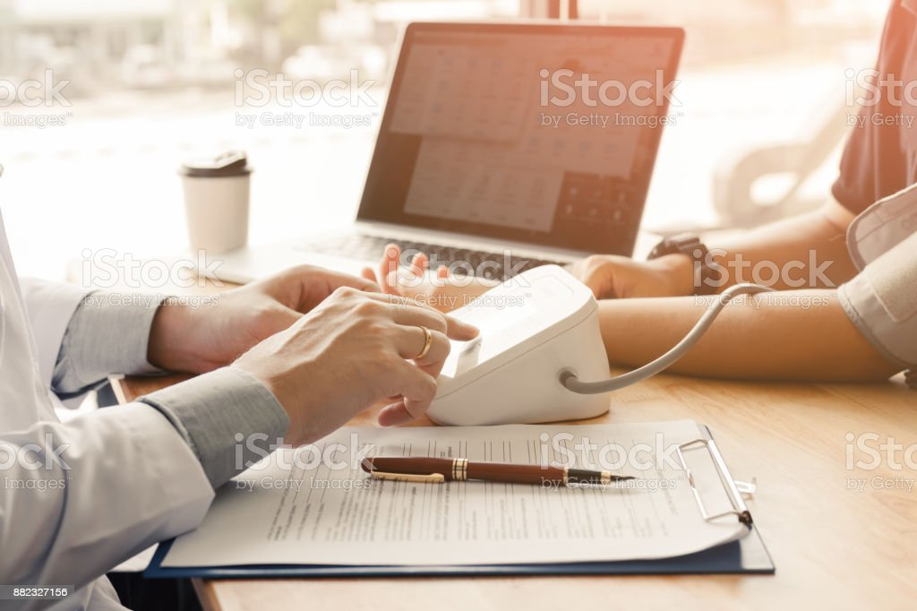 Doctor pressing pressure blood gauge button and talking to patient. stock photo