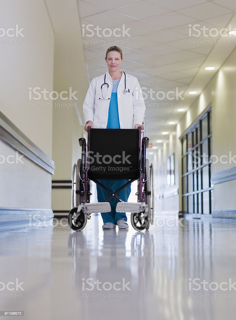 Doctor pushing empty wheelchair royalty-free stock photo