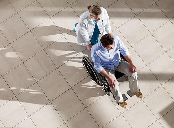 medico spingendo l'uomo in sedia a rotelle - sedia a rotelle foto e immagini stock