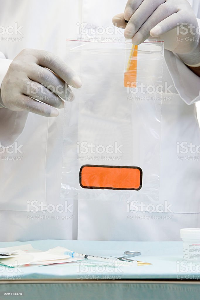 Doctor putting a sample in biohazard bag stock photo