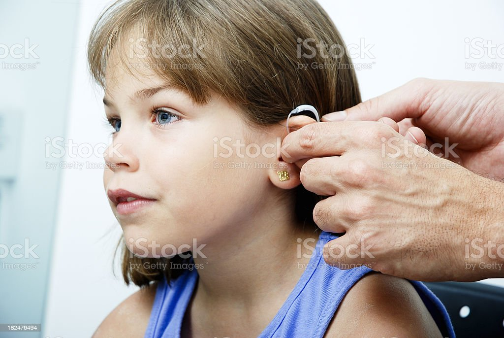 Doctor putting an earhorn in a child's ear stock photo