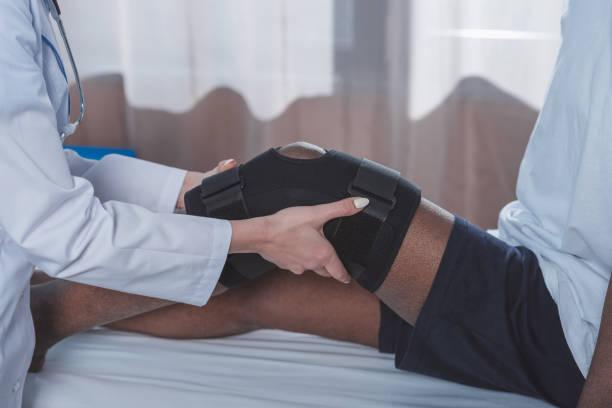 arzt auf knieorthese - orthopädisches hilfsmittel stock-fotos und bilder