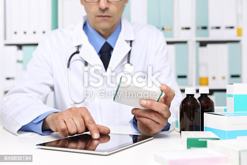 istock Doctor reading a Digital Tablet with drug boxes in hand  at Office Desktop. Health care, Medical and Pharmacy Concept. 649856194