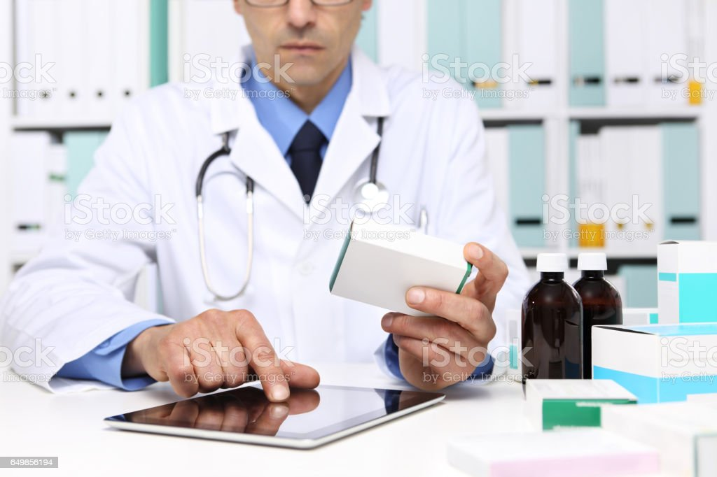 Doctor reading a Digital Tablet with drug boxes in hand  at Office Desktop. Health care, Medical and Pharmacy Concept. - foto de stock