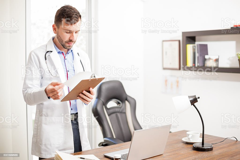 Doctor reading a patient's history in an office stock photo