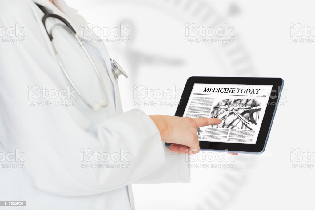 Doctor reading from digital tablet stock photo