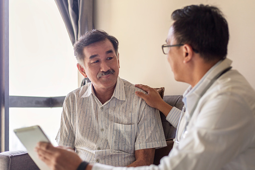 Smiling doctor consoling senior adult patient in medical clinic. Kind caring therapist or caregiver helping older retired man talking, giving comfort, expressing care concept.
