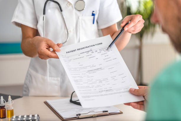 Doctor receiving patient registration form stock photo
