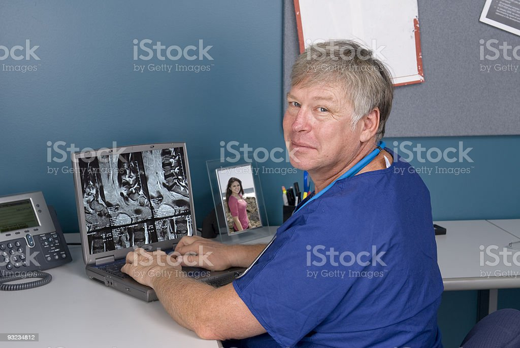 Doctor reviewing MRI on laptop royalty-free stock photo