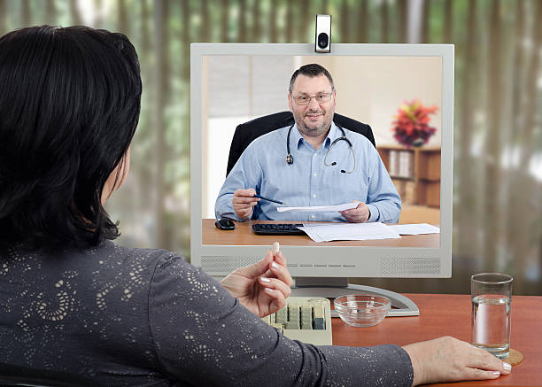 Doctor reviews medical laboratory results with online patient stock photo