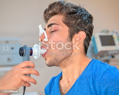 Doctor reviews patient's lung capacity with a peak flow meter