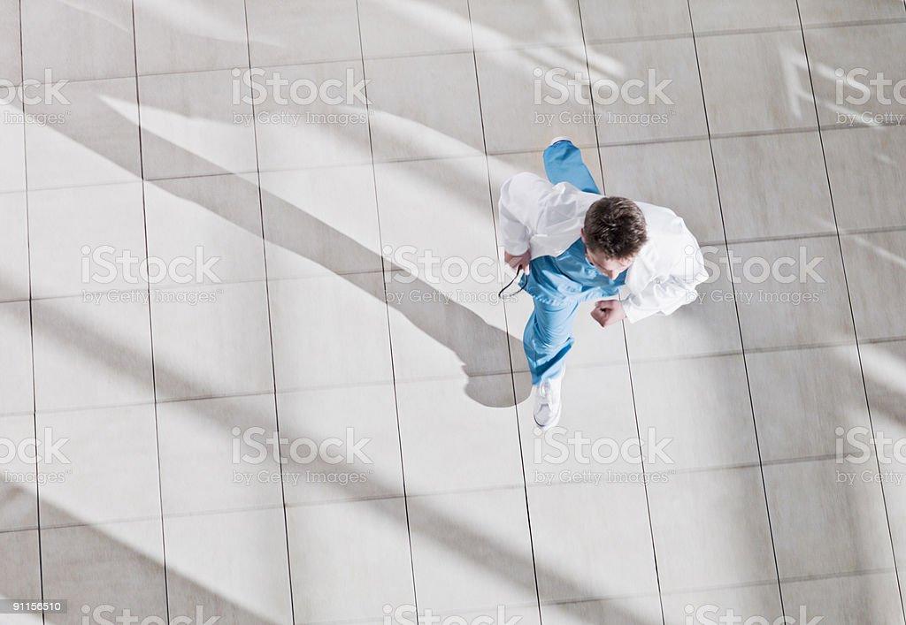 Doctor running through hospital lobby stock photo