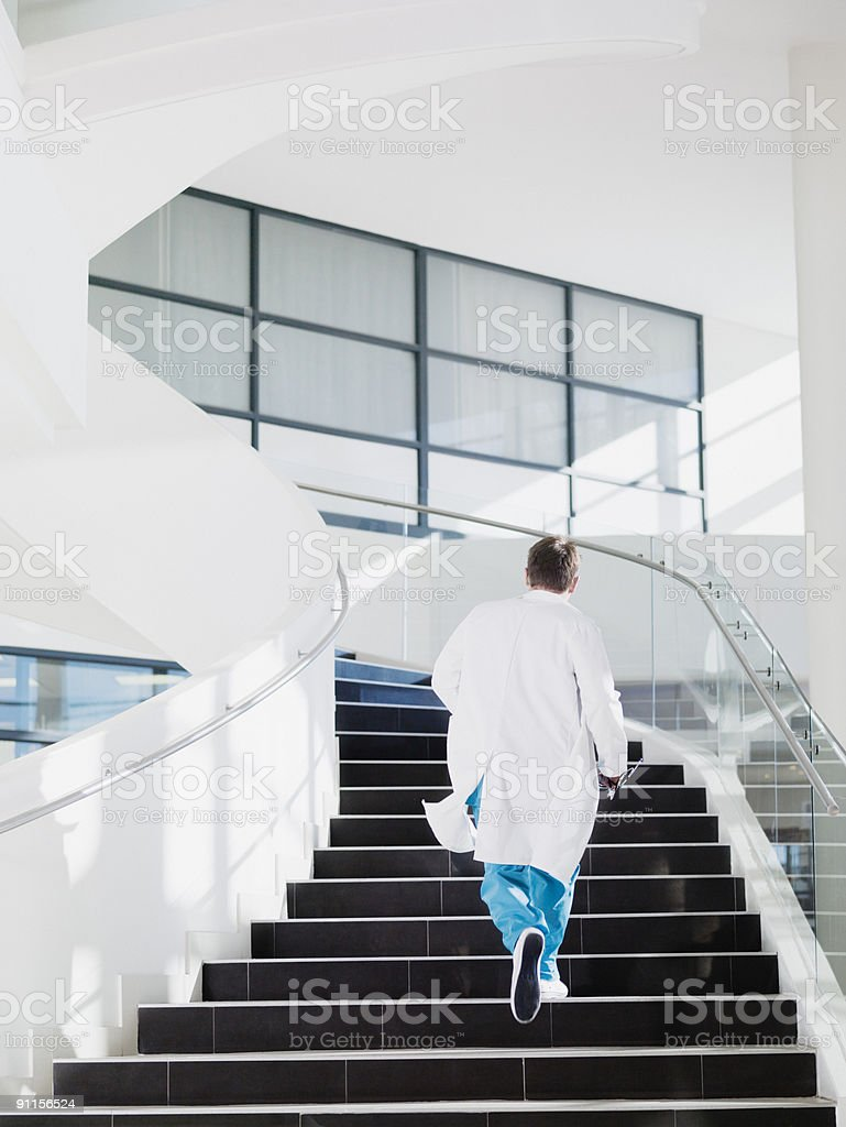Doctor running up hospital staircase stock photo
