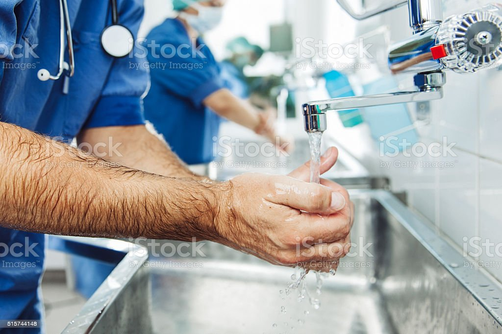 Doctor scrubbing in at hospital stock photo