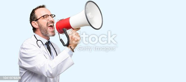 istock Doctor senior man, medical professional communicates shouting loud holding a megaphone, expressing success and positive concept, idea for marketing or sales 1041976328
