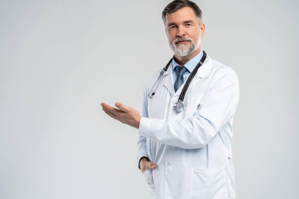 Arzt Senior Mann, Medizinischer Fachmann hält etwas in leerer Hand isoliert über weißen Hintergrund. – Foto