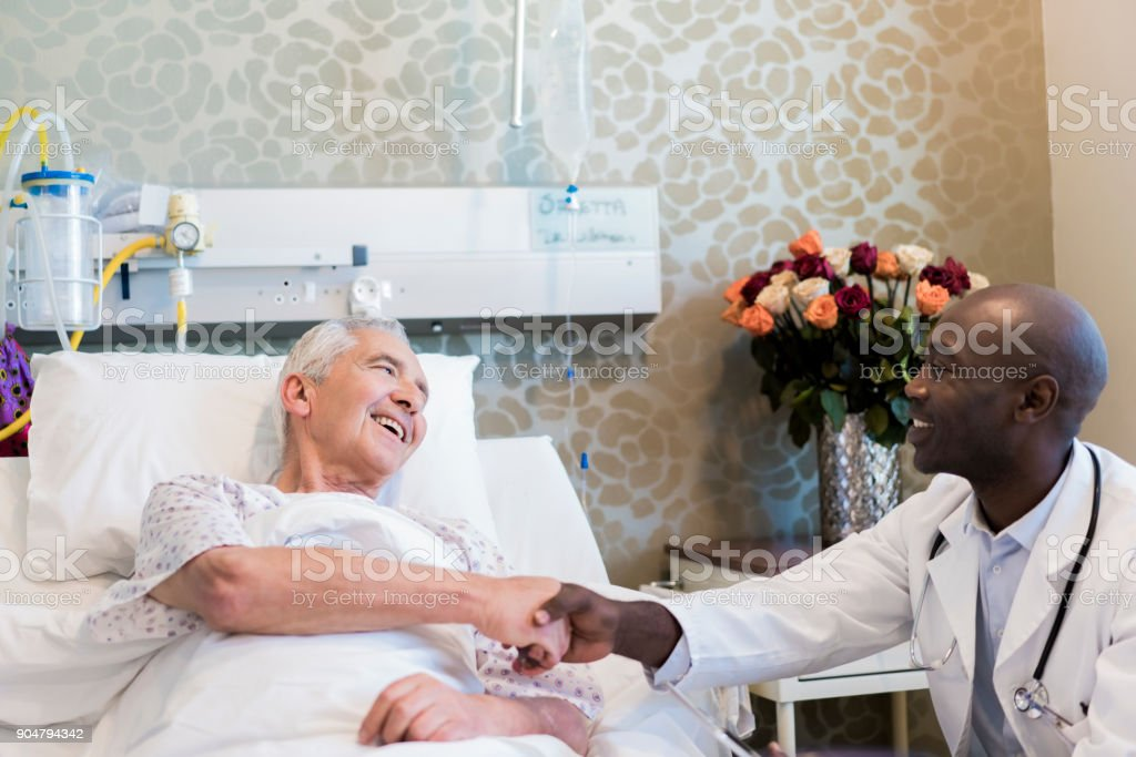 Doctor shaking hands with smiling senior patient stock photo