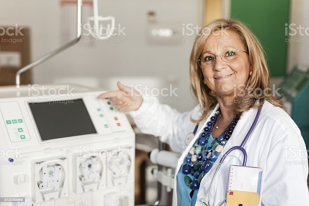 Doctor showing a dialyser stock photo