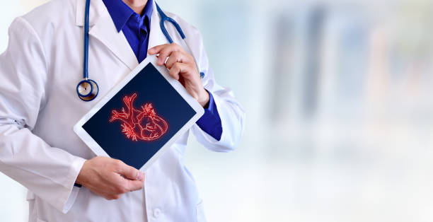 Doctor showing a heart on a tablet in hospital stock photo