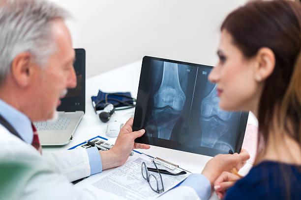 Médico mostrando una radiografía de la paciente - foto de stock