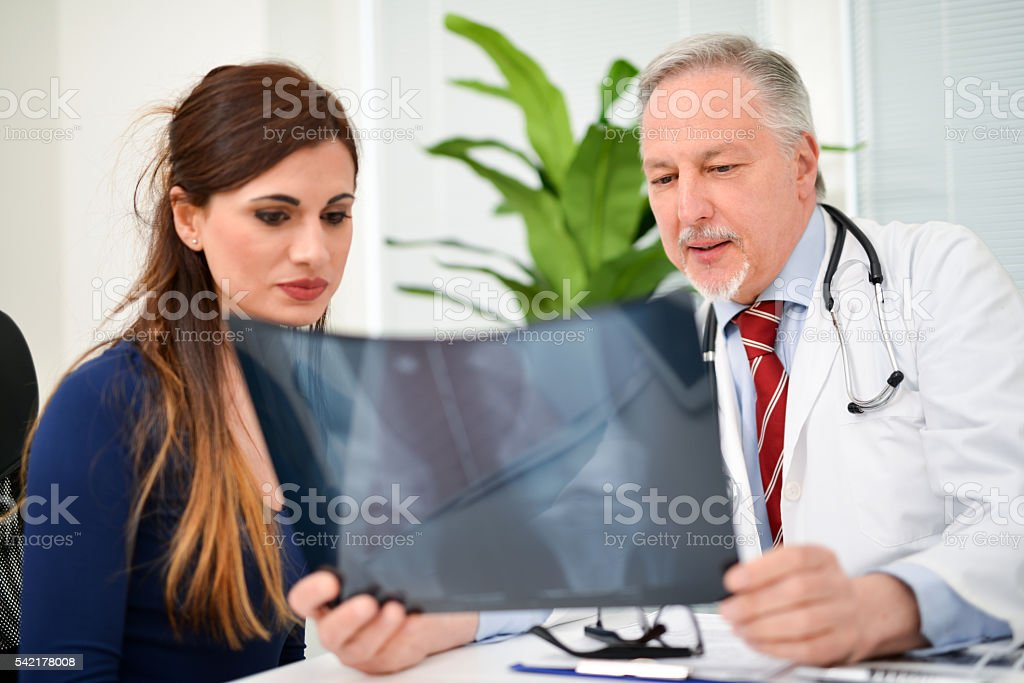 Doctor showing a radiography to his patient stock photo