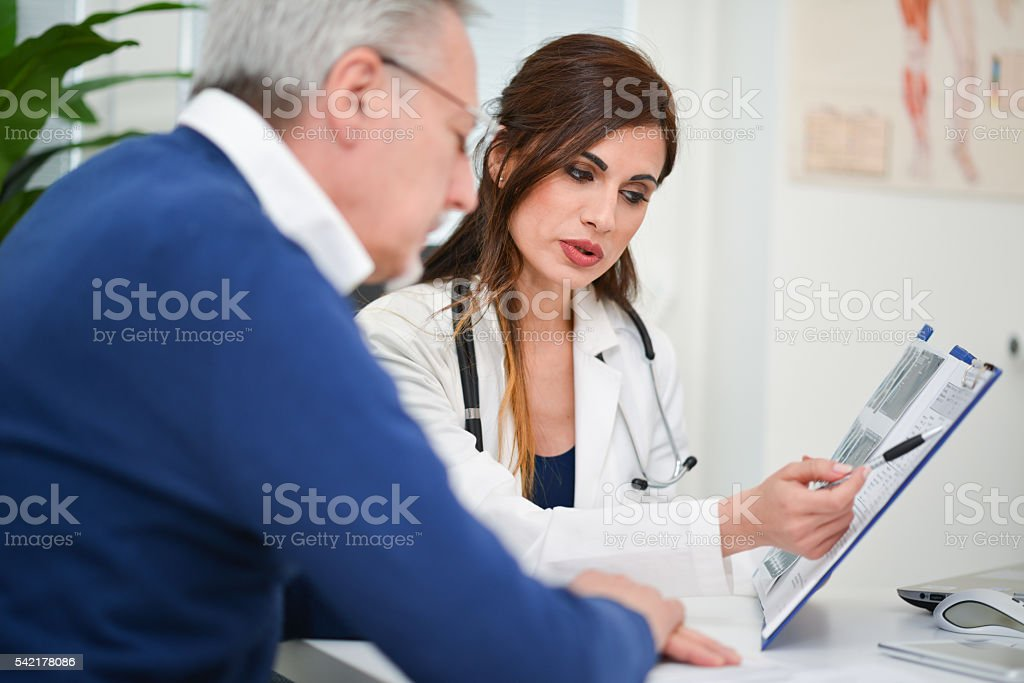 Doctor showing an examination report to a patient stock photo