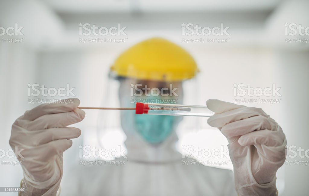 Doctor showing covid-19 tube test and sampling swab On woman, female doctor in protective suit holding and showing covid-19 tube test and sampling swab. Accidents and Disasters Stock Photo