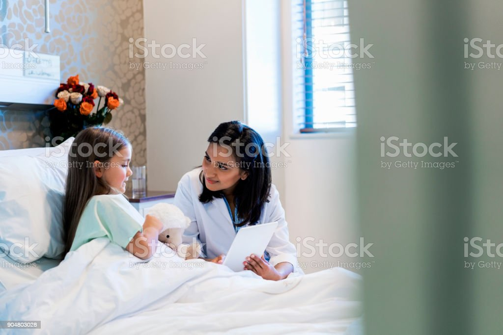 Doctor showing digital tablet to patient stock photo
