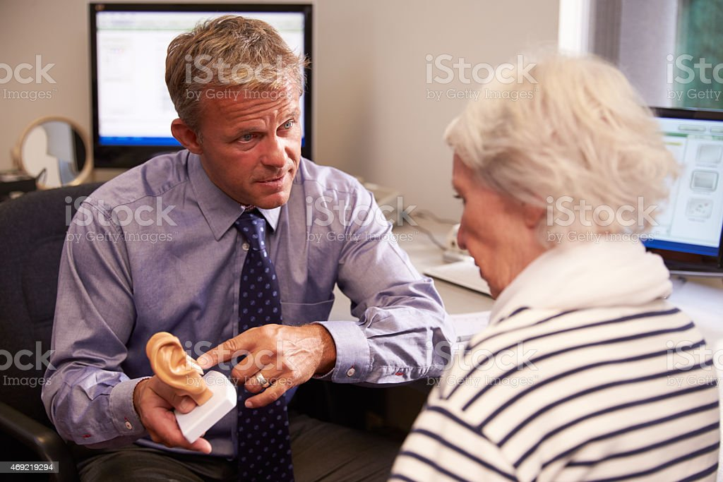 Doctor showing female patient a model of the human ear stock photo