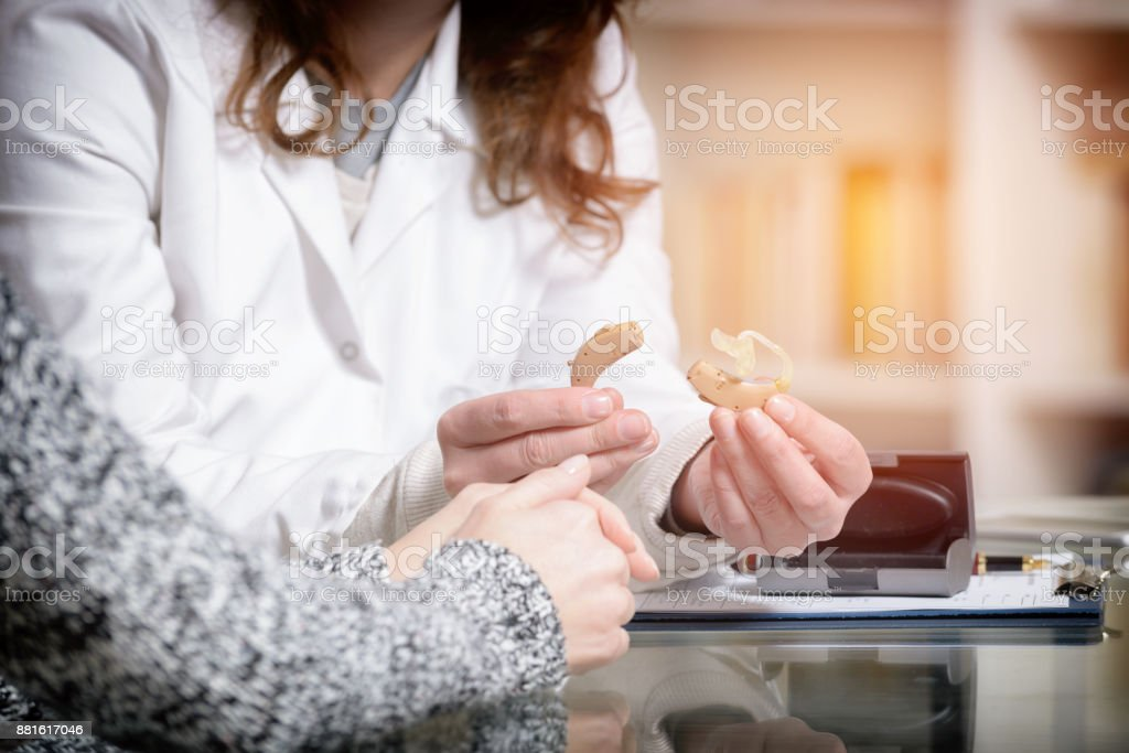 Doctor showing hearing aid stock photo