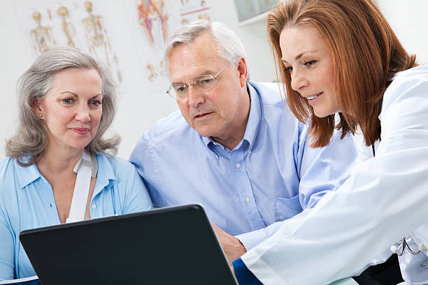 Doctor Showing Medical Data To Adult Patient And Her Spouse