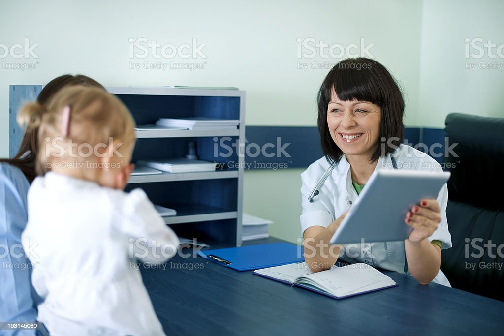 Doctor showing mother's medical results on the tablet royalty-free stock photo