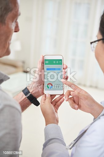 istock Doctor showing patient health tracking app 1035512848