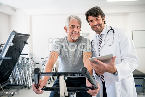 istock Doctor showing patient recovery plan while he is working out on a static bicycle 912334116
