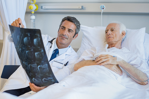 1049772134 istock photo Doctor showing patient xray 667831950