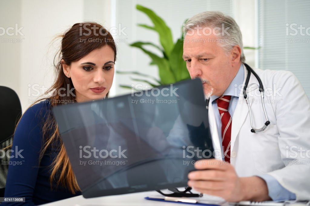 Doctor showing radiography to a patien stock photo