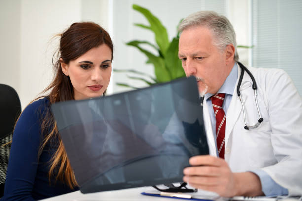 doctor showing radiography to a patien - osteoporosi foto e immagini stock