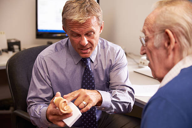 Doctor Showing Senior Male Patient Model Of Human Ear stock photo