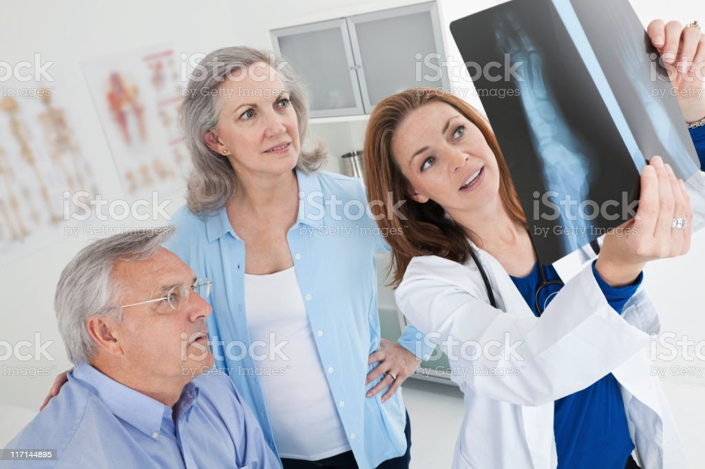 Doctor Showing X-Ray Results to Mature Adult Couple royalty-free stock photo