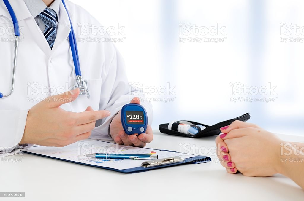 Doctor shows glucometer with glucose level stock photo