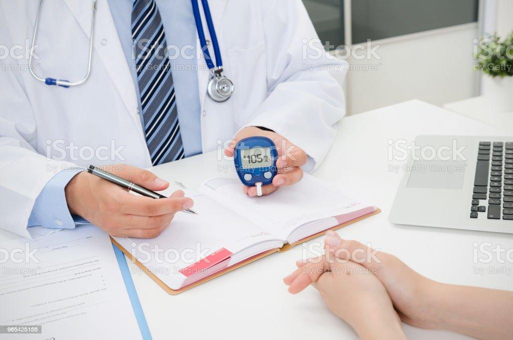 Doctor shows glucometer with glucose level - Zbiór zdjęć royalty-free (Analizować)