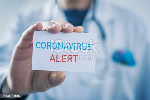 closeup of a caucasian doctor man showing a sign with the text coronavirus alert written in it