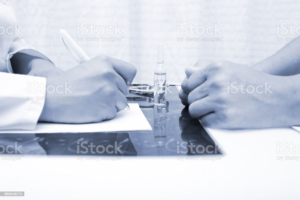 Doctor signs the treatment for the patient during medical appointment royalty-free stock photo