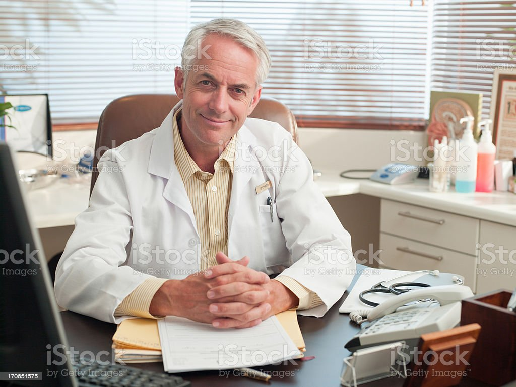 Doctor sitting at desk in office royalty-free stock photo
