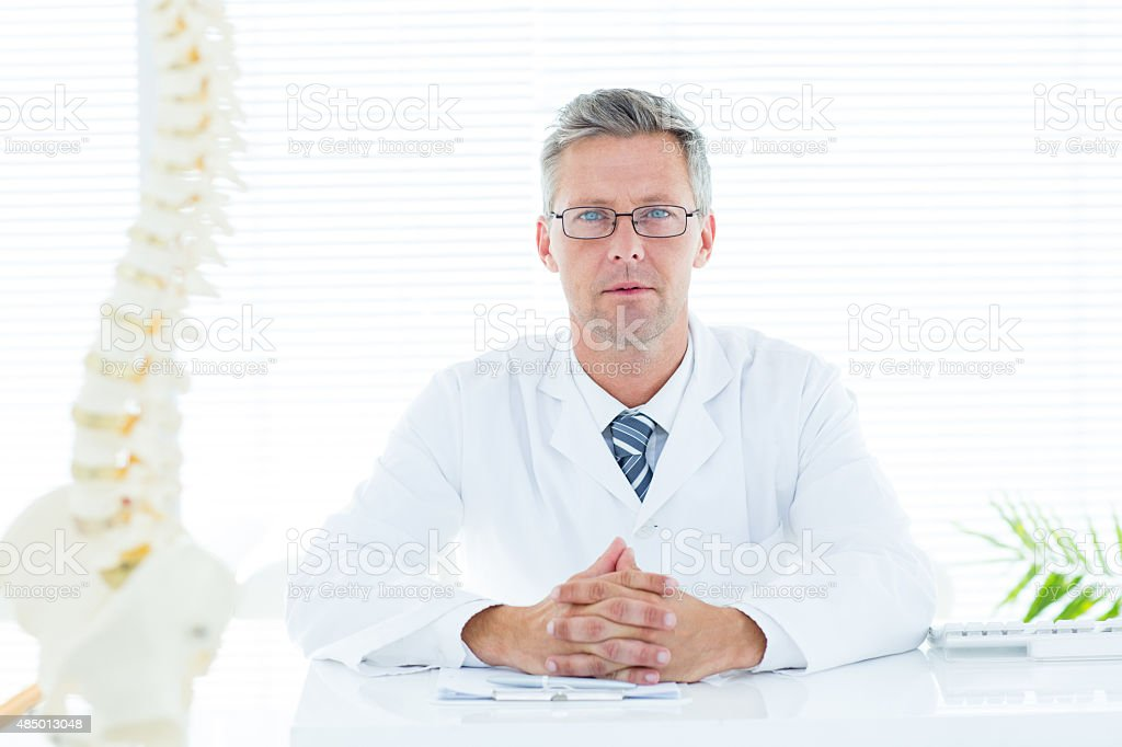 Doctor sitting at his desk stock photo