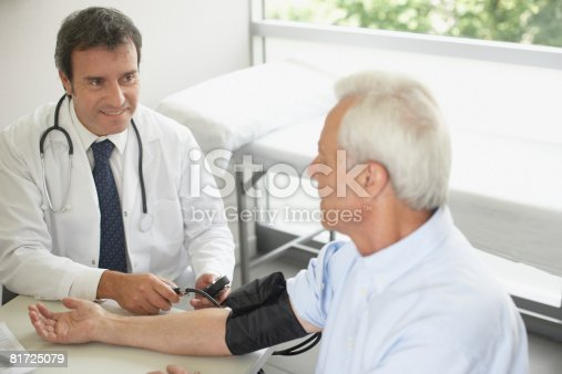 istock Doctor sitting in office with patient taking blood pressure and smiling 81725079